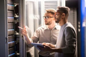 2 male IT professionals solving network server problems